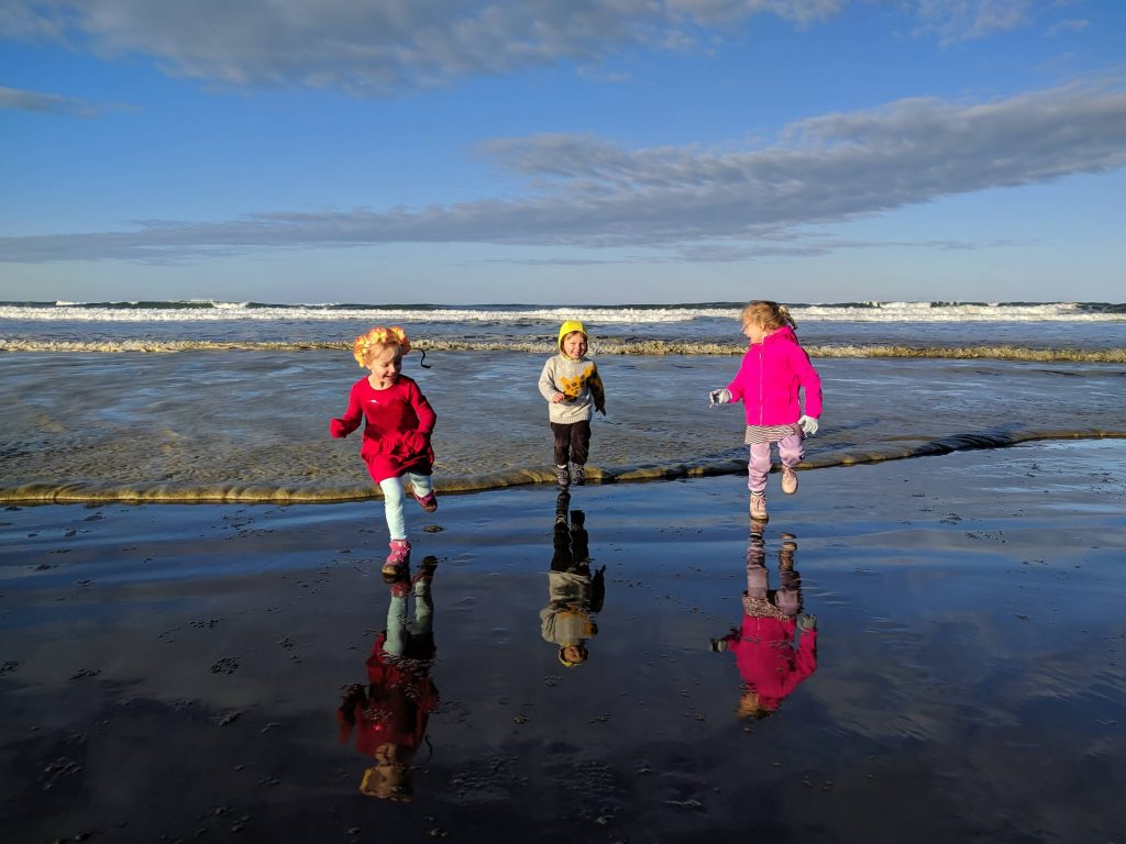 Kids running from the waves of the Pacific